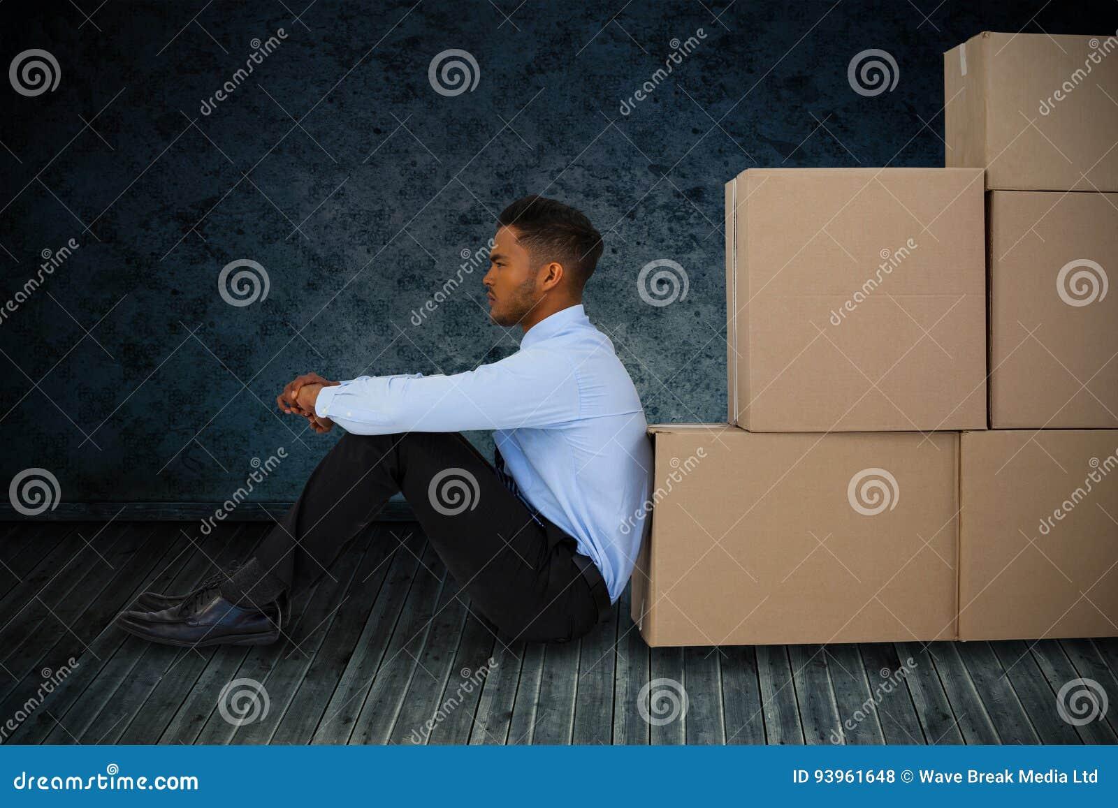 Imagen compuesta del hombre de negocios que se inclina en las cajas de cartón contra el fondo blanco