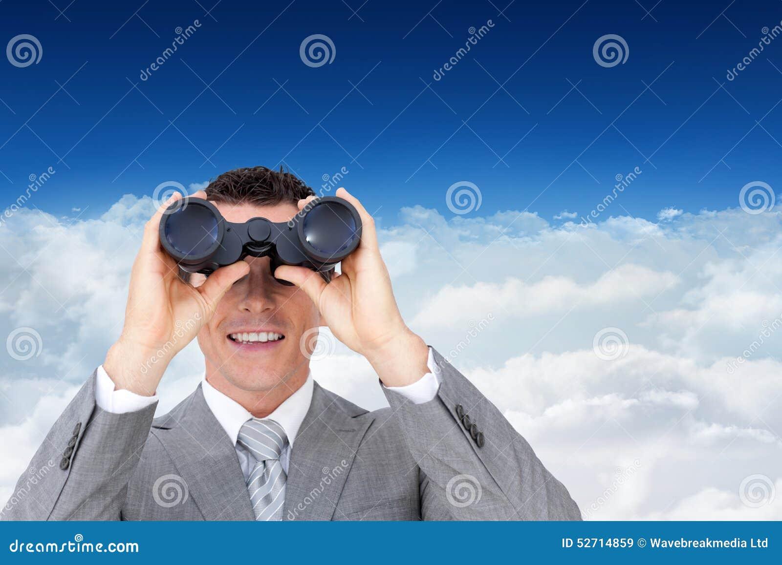 Imagen compuesta del hombre de negocios que sostiene los prismáticos