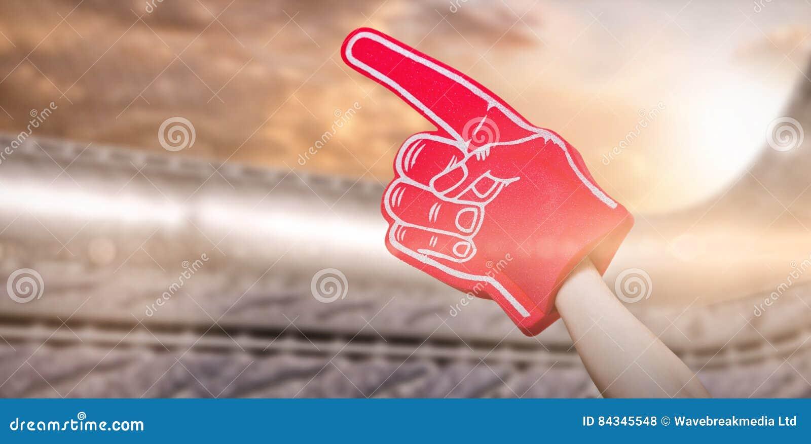 Imagen compuesta del jugador de fútbol americano que celebra la mano 3d de la espuma del partidario