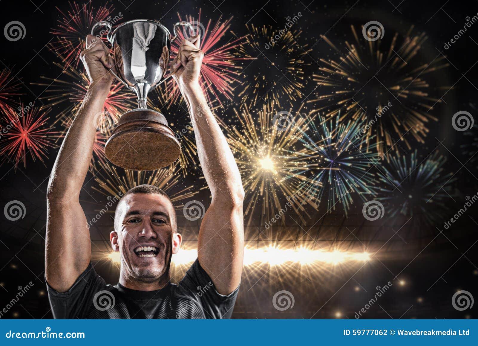 Imagen compuesta del retrato del jugador acertado del rugbi que celebra el trofeo
