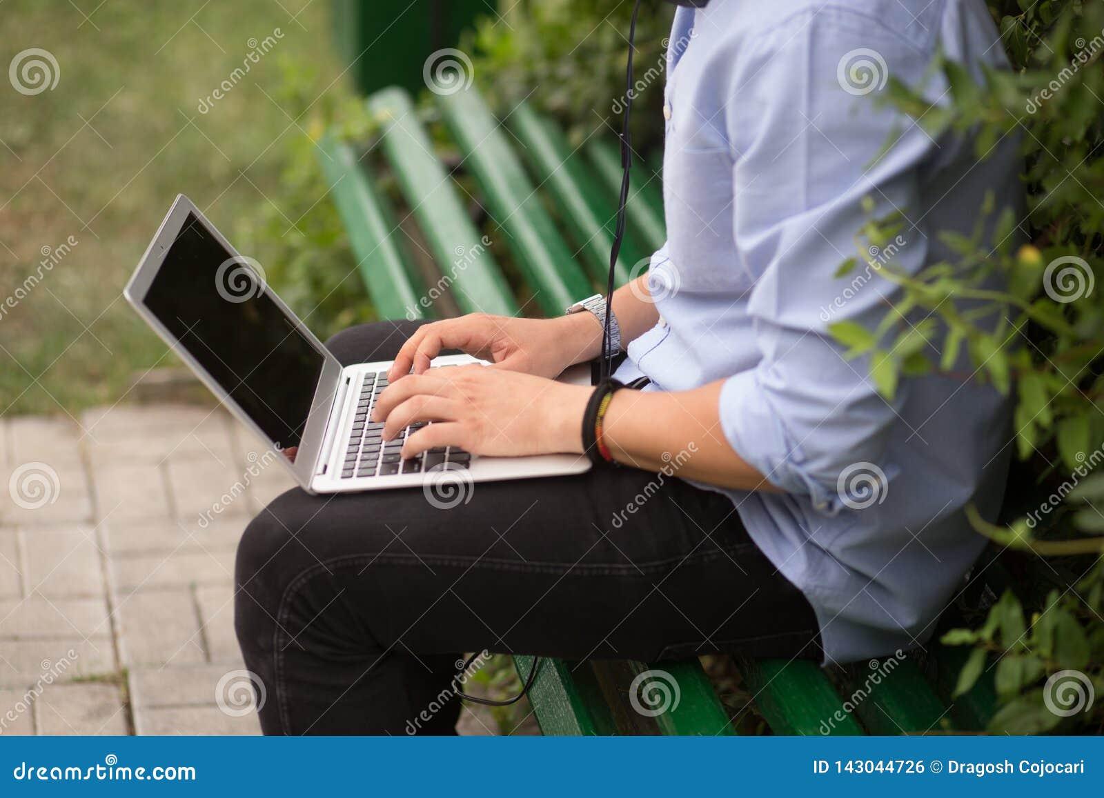 Imagen cosechada del hombre joven que se sienta en el banco en el parque, usando un ordenador portátil