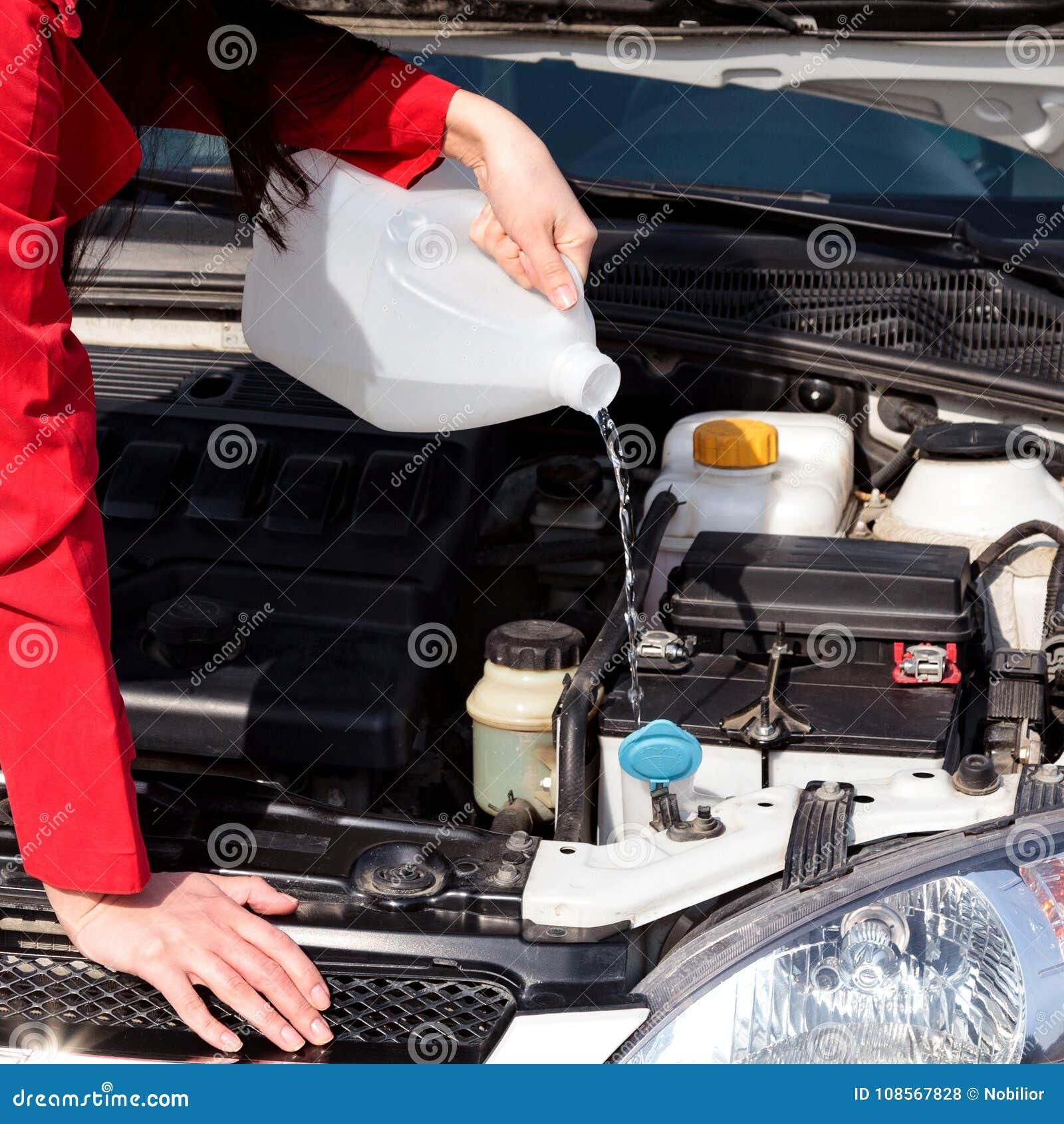 Imagen cosechada del líquido de colada de la lavadora del parabrisas de la mujer