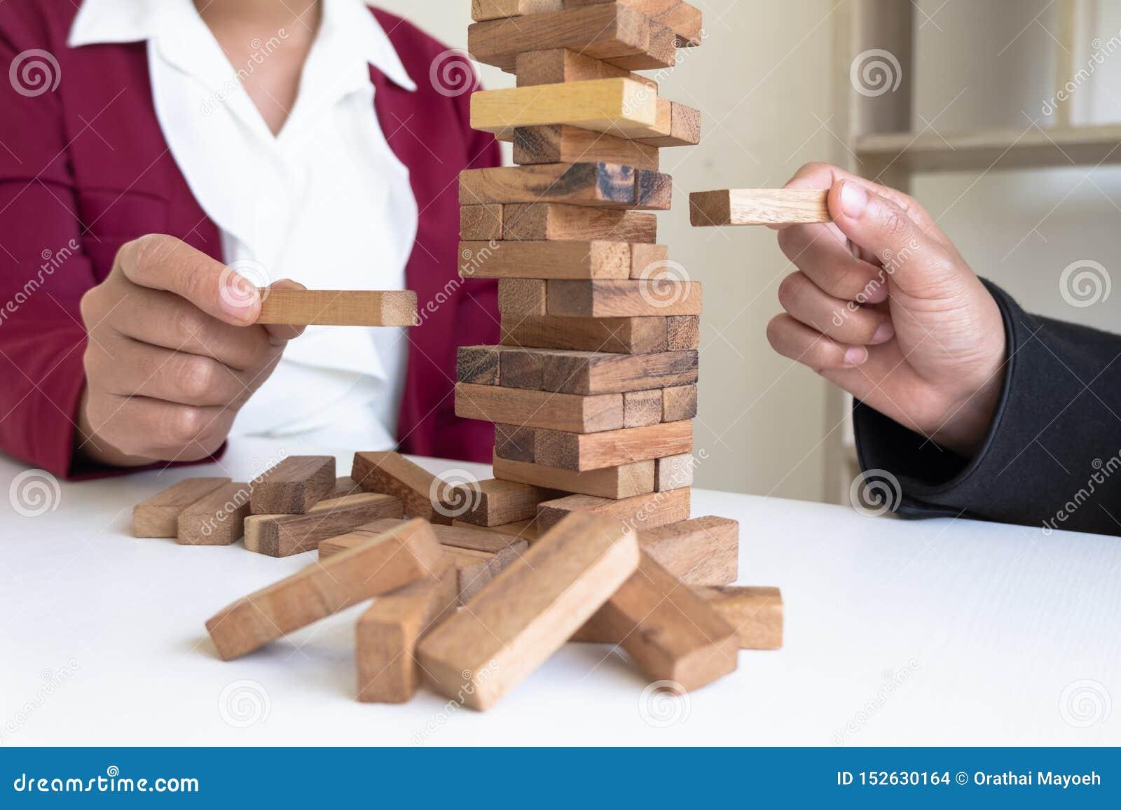Imagen de la mano que lleva a cabo el juego de madera de los bloques a crecer del negocio Riesgo de plan de gestión y de la estra