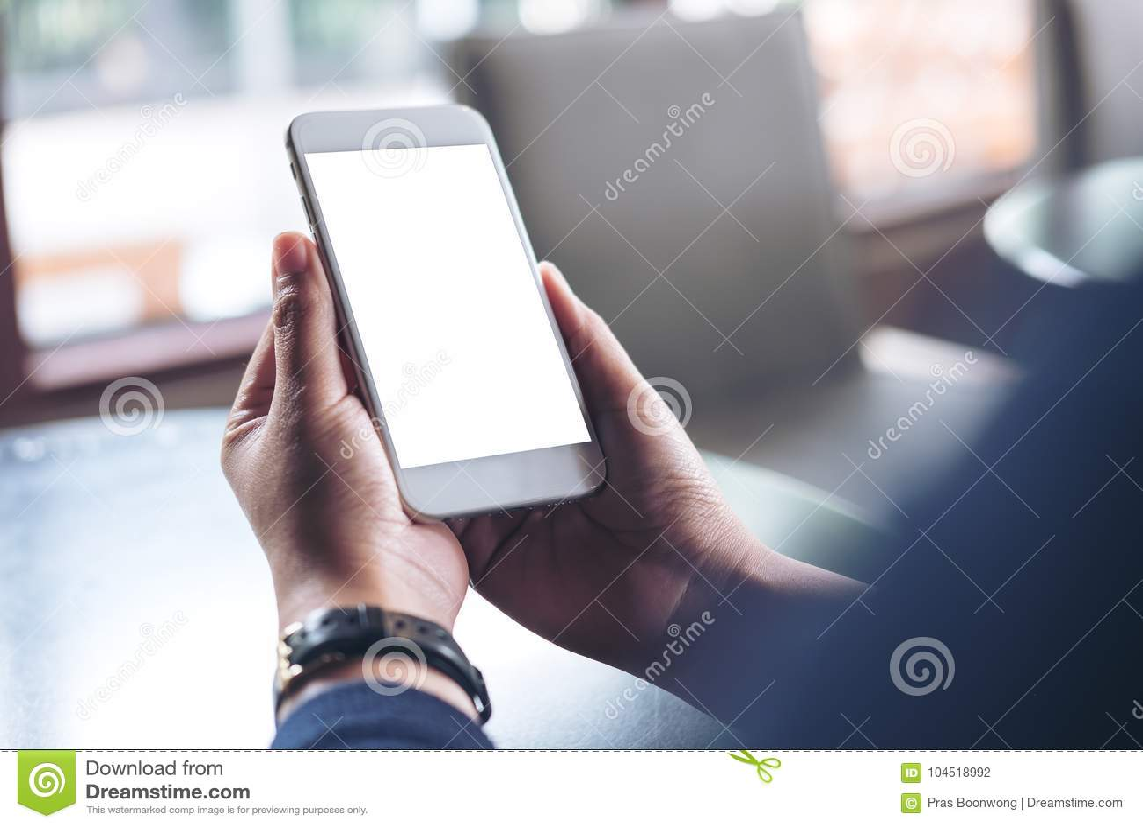 Imagen de la maqueta de las manos que sostienen el teléfono móvil con la pantalla blanca en blanco