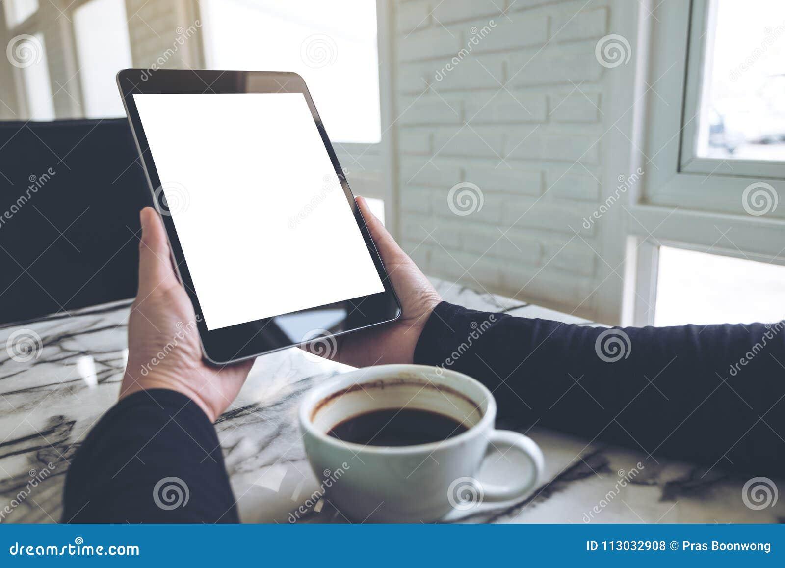 Imagen de la maqueta de las manos que sostienen la PC negra de la tableta con la taza blanca en blanco de la pantalla y de café e