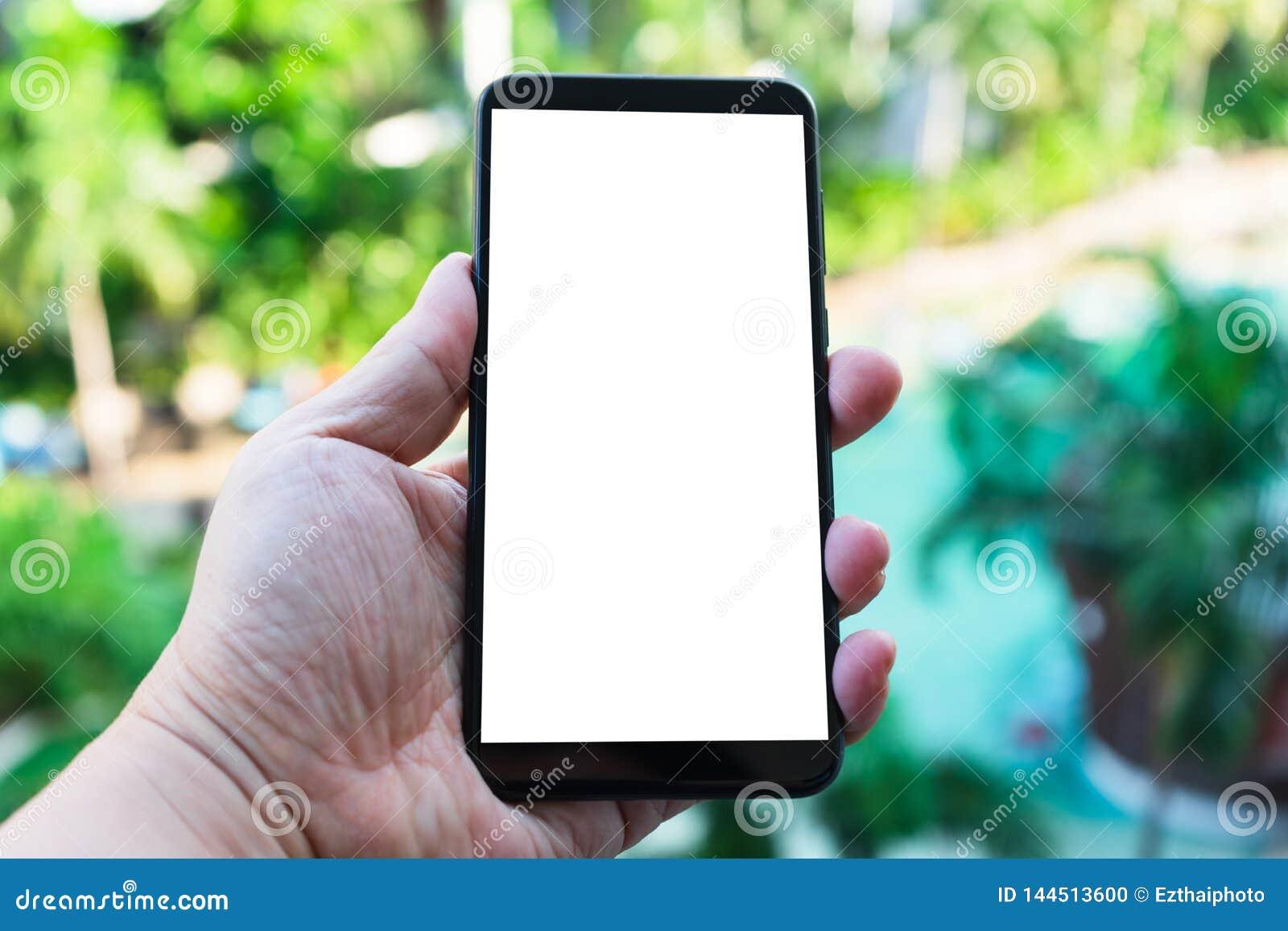 Imagen de la maqueta de la mano que sostiene el nuevo teléfono móvil negro con la pantalla en blanco con el fondo verde del bok