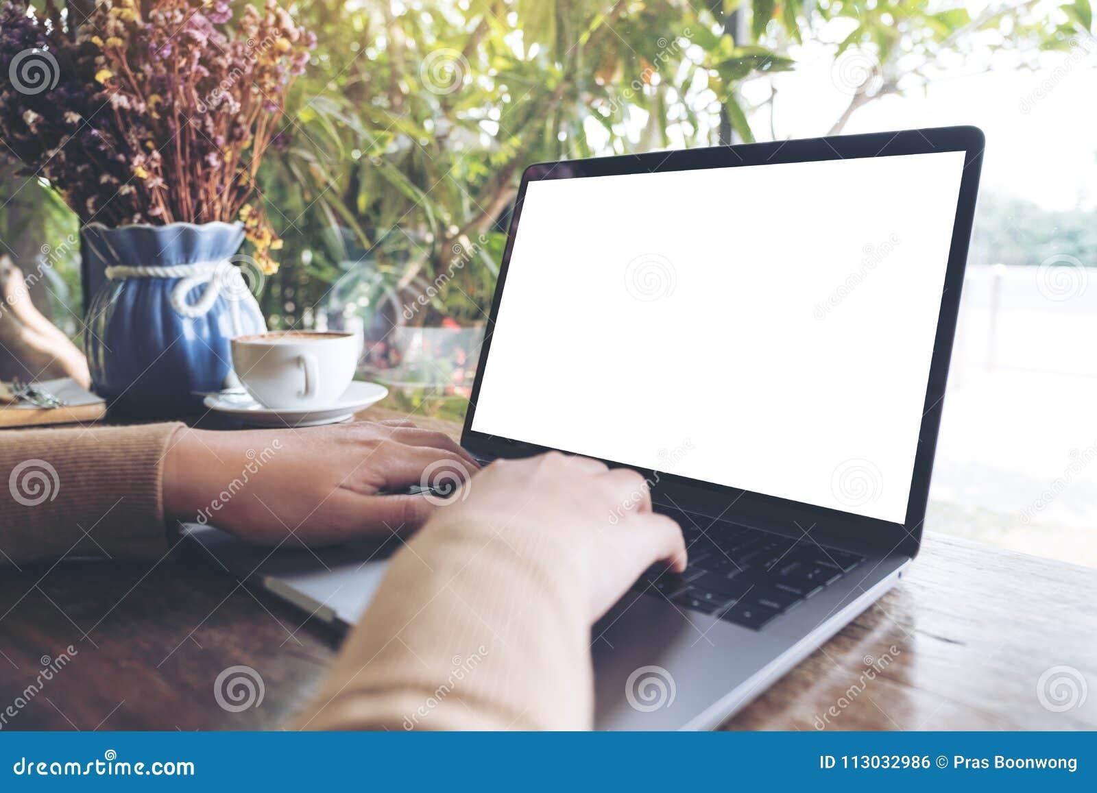 Imagen de la maqueta de manos usando y mecanografiando en el ordenador portátil con la pantalla de escritorio blanca en blanco en
