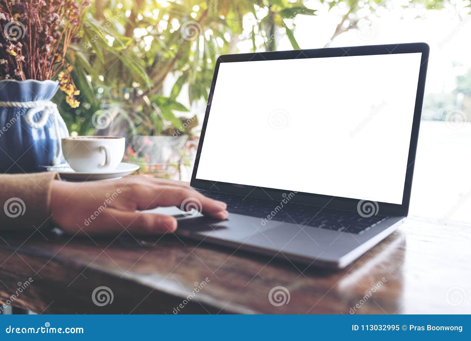 Imagen de la maqueta de manos usando y tocando en el ordenador portátil con la pantalla de escritorio blanca en blanco en la tabl