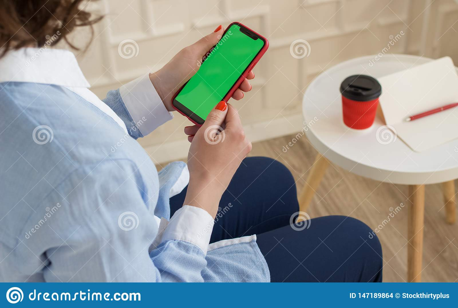 Imagen de la maqueta: muchacha adentro en camisa azul y los pantalones que sostienen el teléfono móvil negro con la pantalla domi