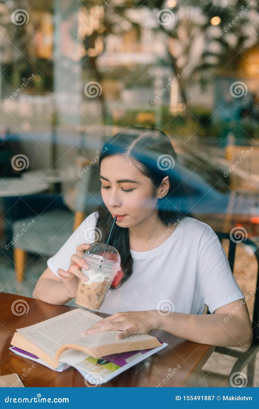 Imagen de la mujer bonita joven que se sienta en la tabla en caf? y libro de lectura