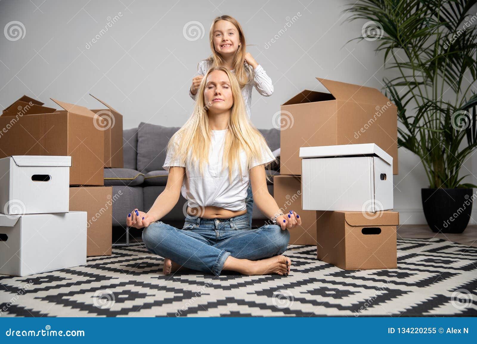 Imagen de la mujer tranquila que se sienta en piso entre las cajas y la muchacha de cartón que saltan en el sofá