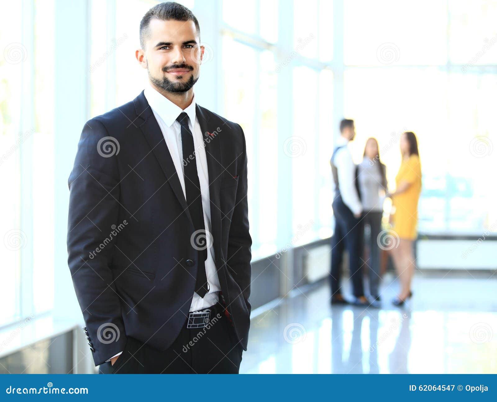 Imagen de los hombres de negocios jovenes elegantes que miran la cámara