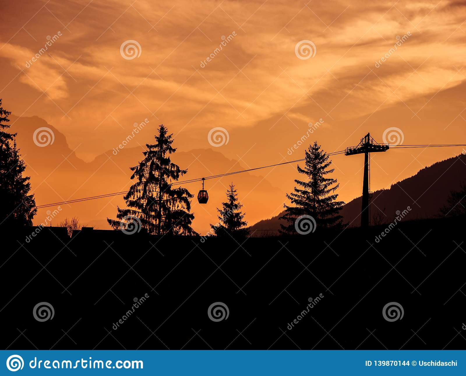 Imagen de siluetas del remonte y de los árboles durante salida del sol en la madrugada