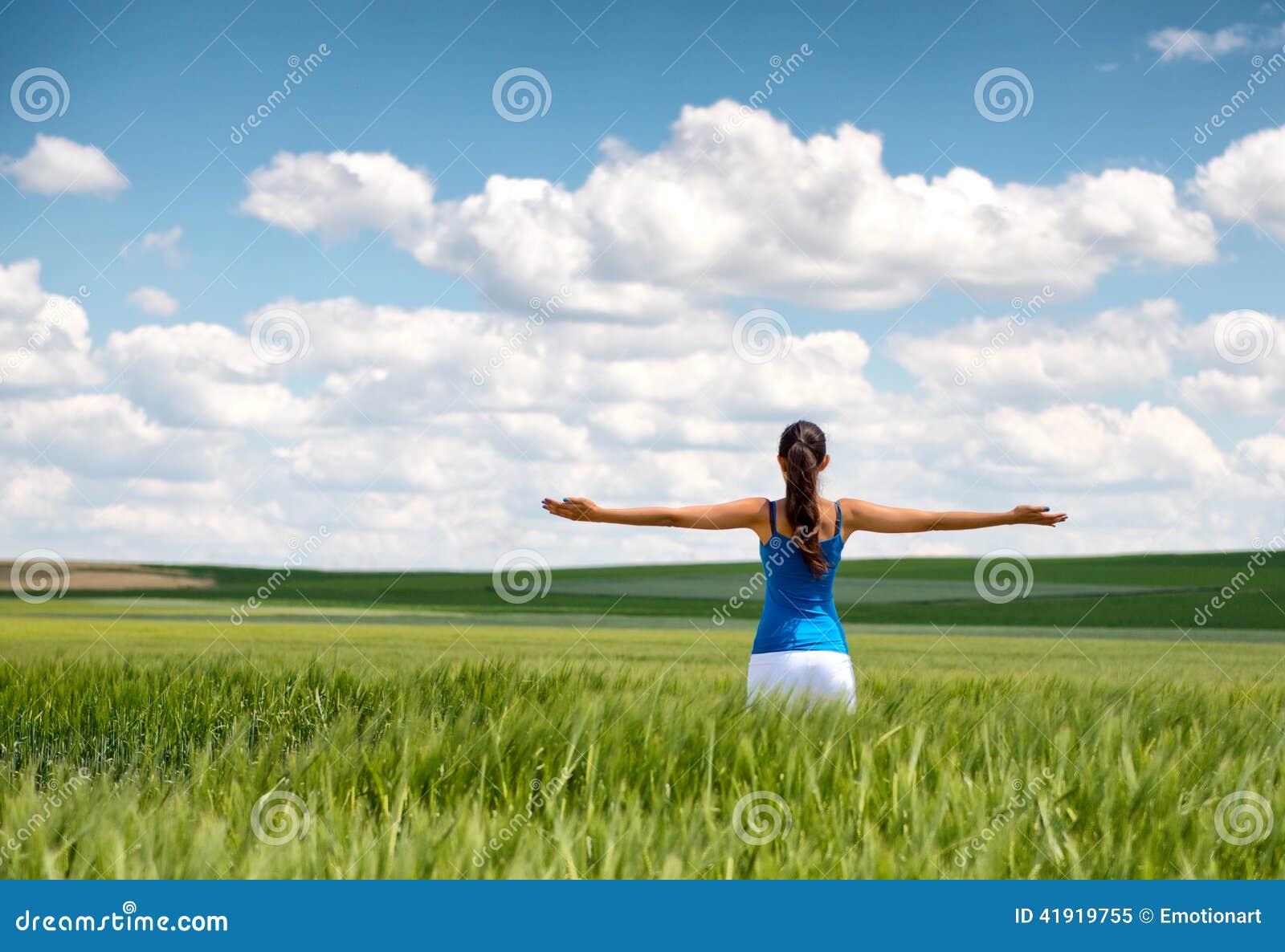 Imagen de una muchacha en un campo de trigo con los brazos separados