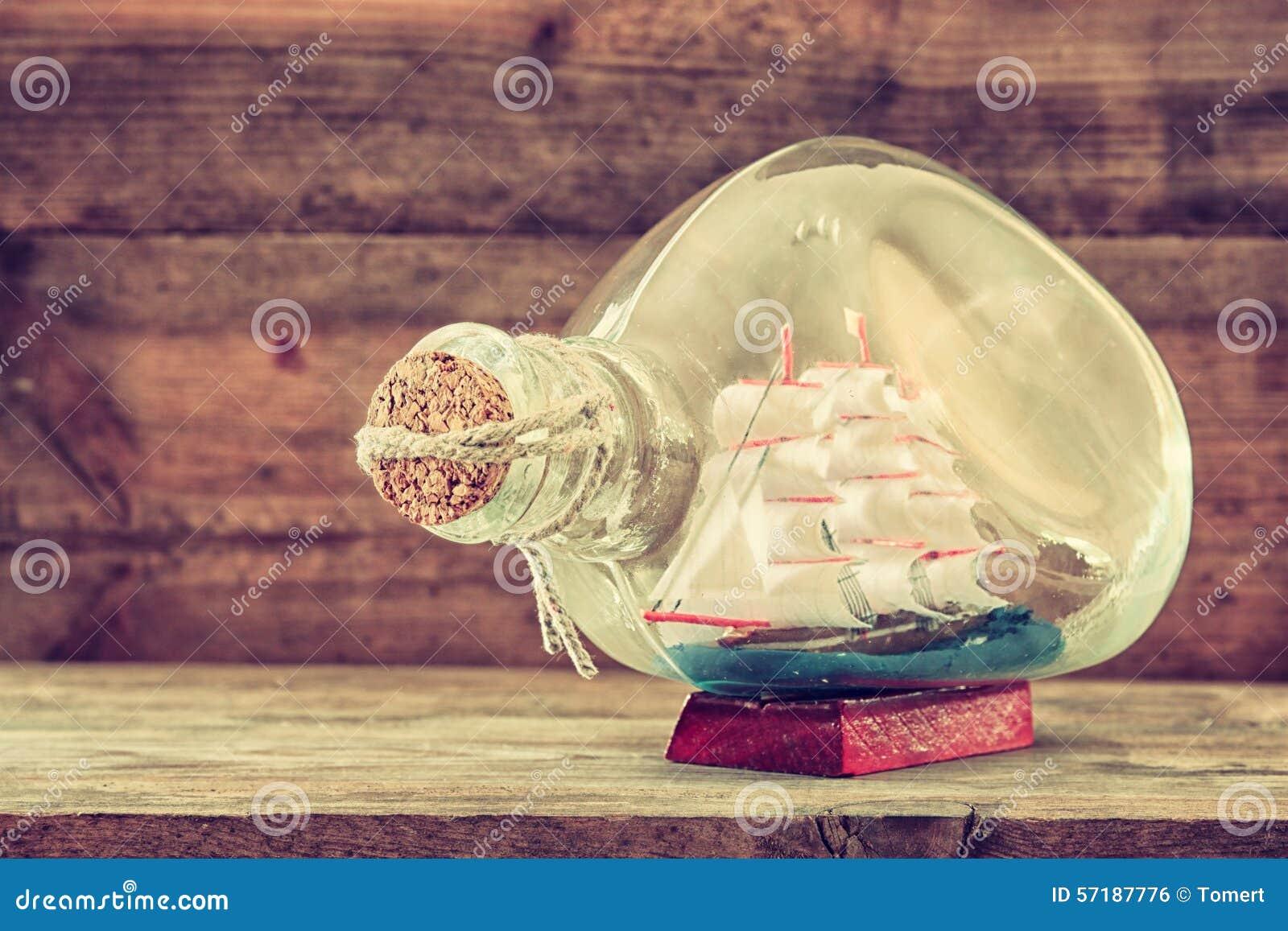 Imagen del barco decorativo en la botella en la tabla de madera Concepto náutico imagen filtrada retra