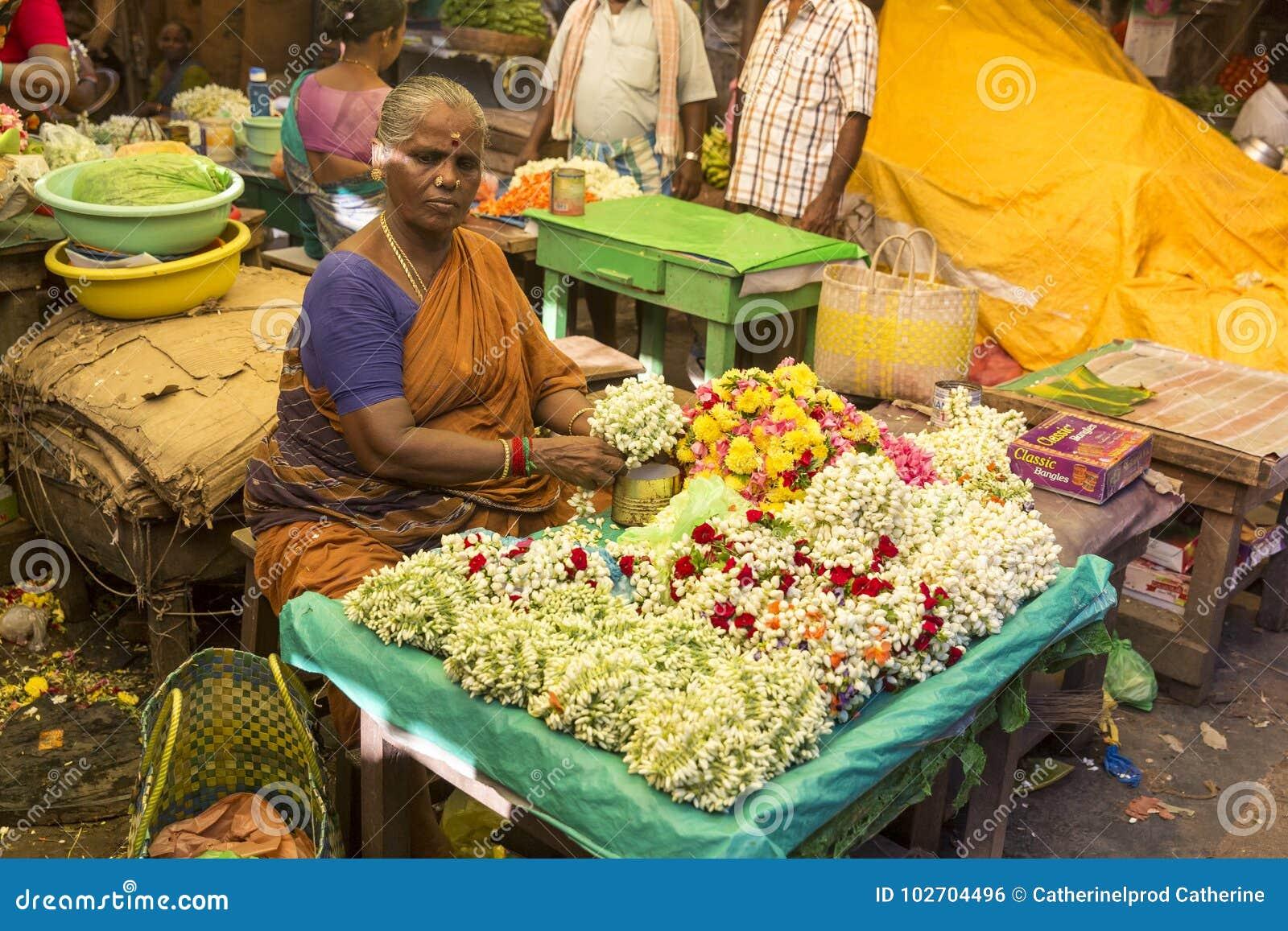Imagen del editorial de Documetary Venta no identificada de la mujer del hombre que crea cuerdas de flores en el mercado principa