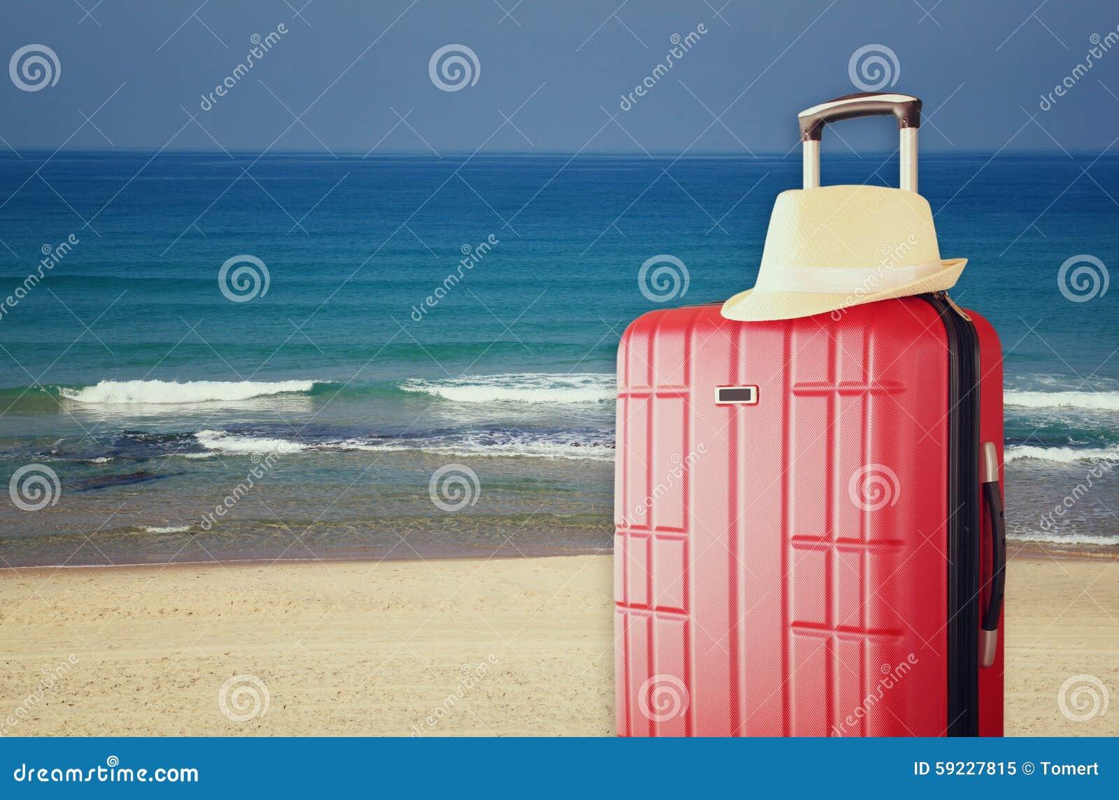 Imagen del equipaje del viaje y del sombrero elegantes rojos del sombrero de ala delante del mar Concepto del viaje y de las vaca