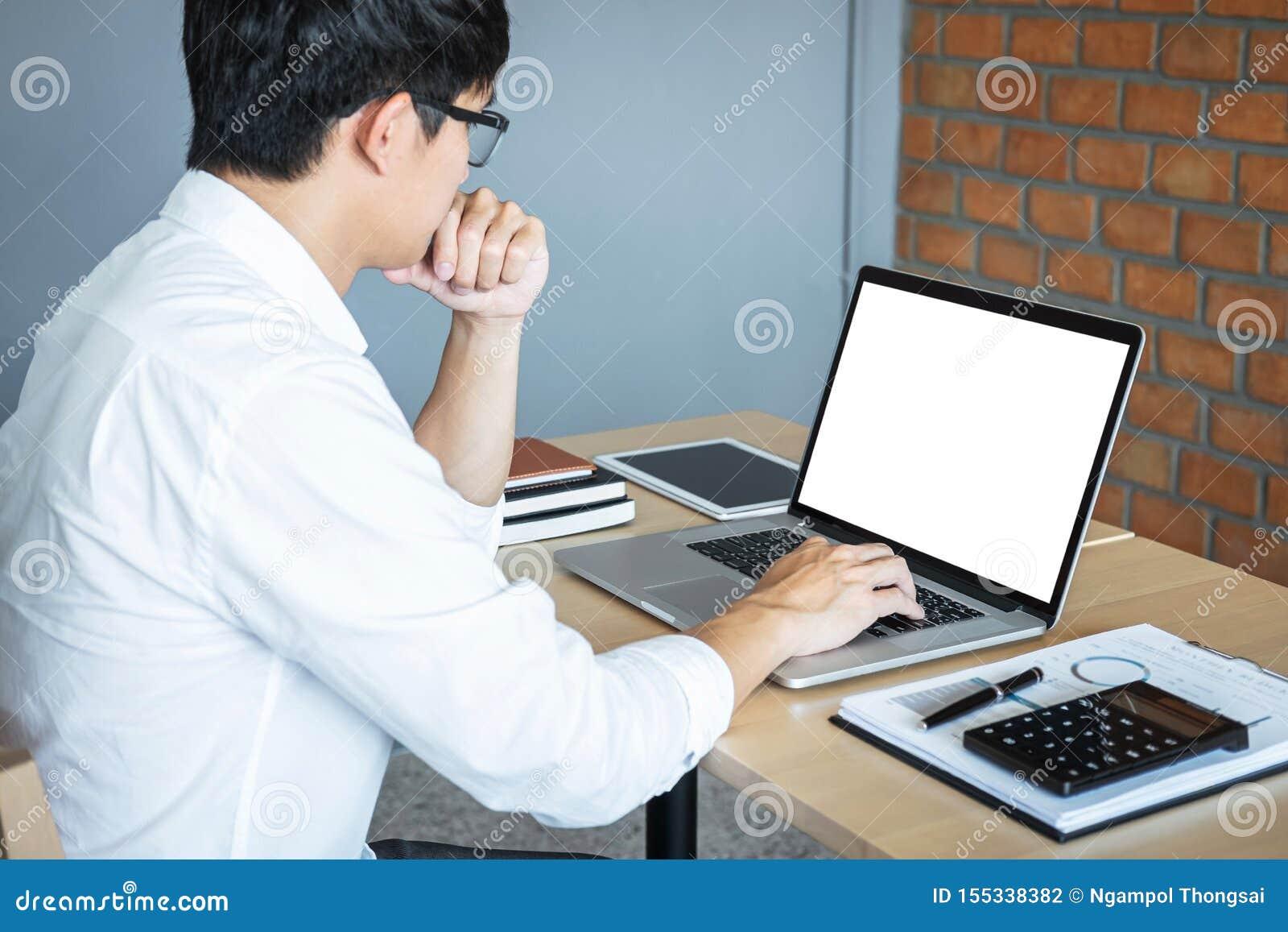 Imagen del hombre joven que trabaja delante del ordenador portátil que mira la pantalla con una pantalla blanca limpia y el espac
