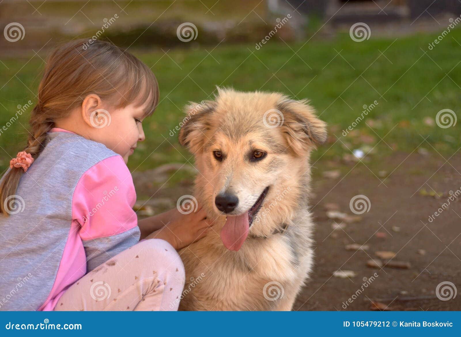 Imagen del perro de perrito blanco conmovedor de la niña que pone en la tierra del parque