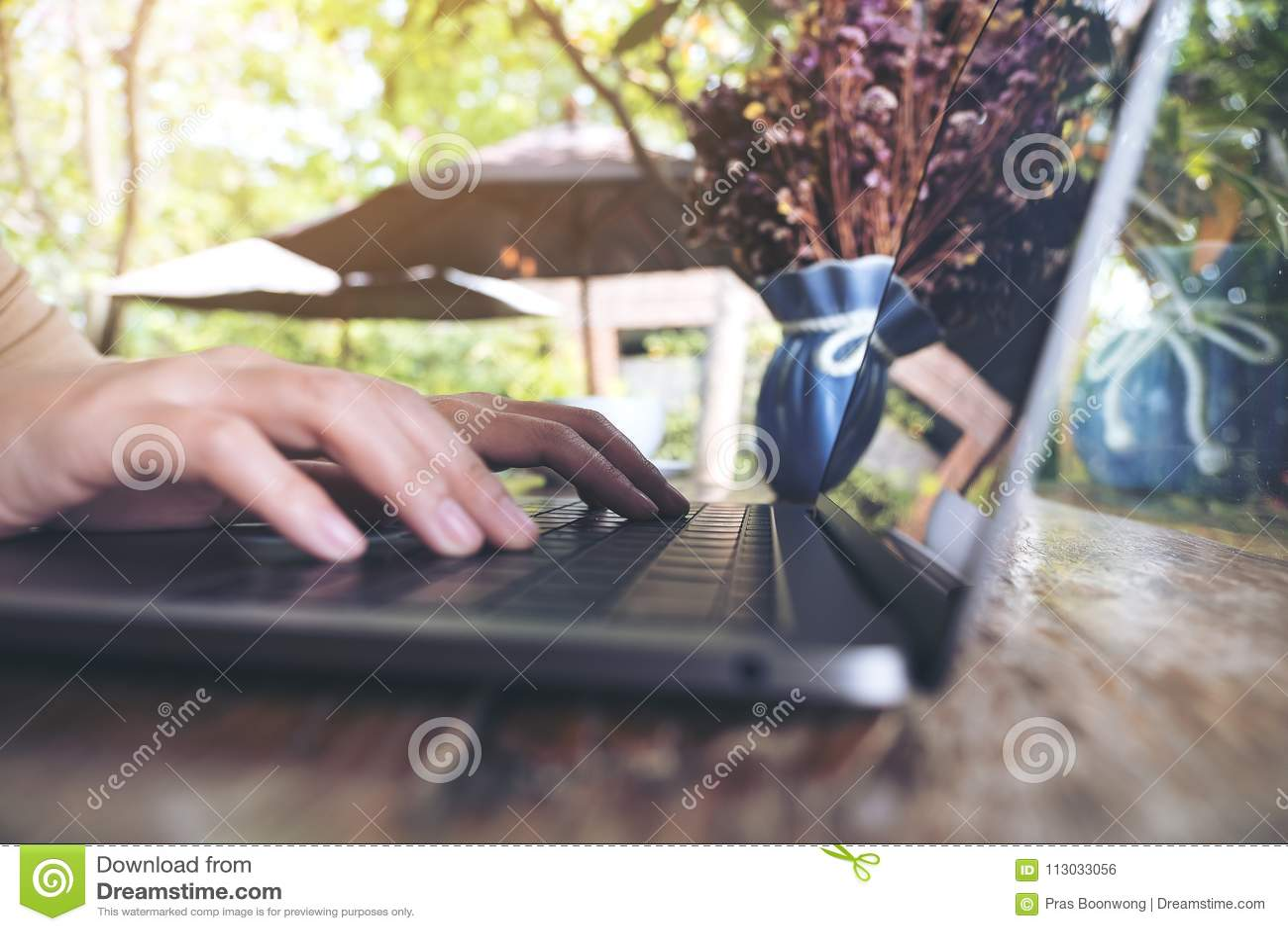 Imagen del primer de las manos que trabajan y que mecanografían en el teclado del ordenador portátil en la tabla de madera