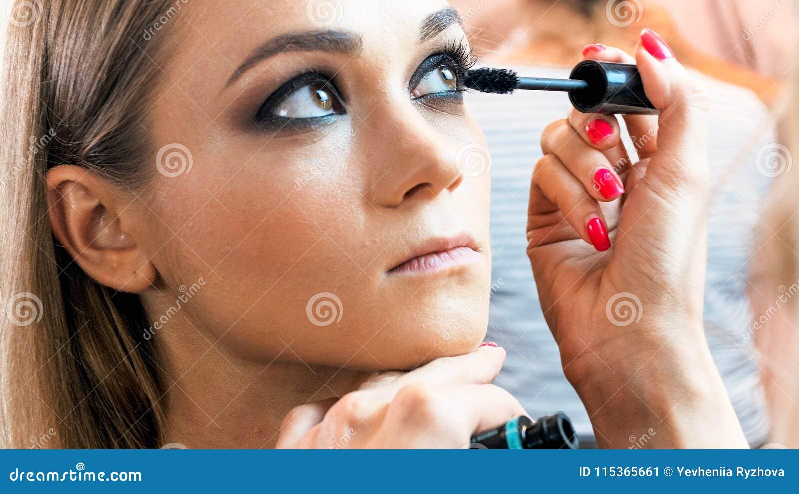 Imagen del primer de las pestañas del ` s del modelo de la pintura del artista de maquillaje del profesinal con rimel