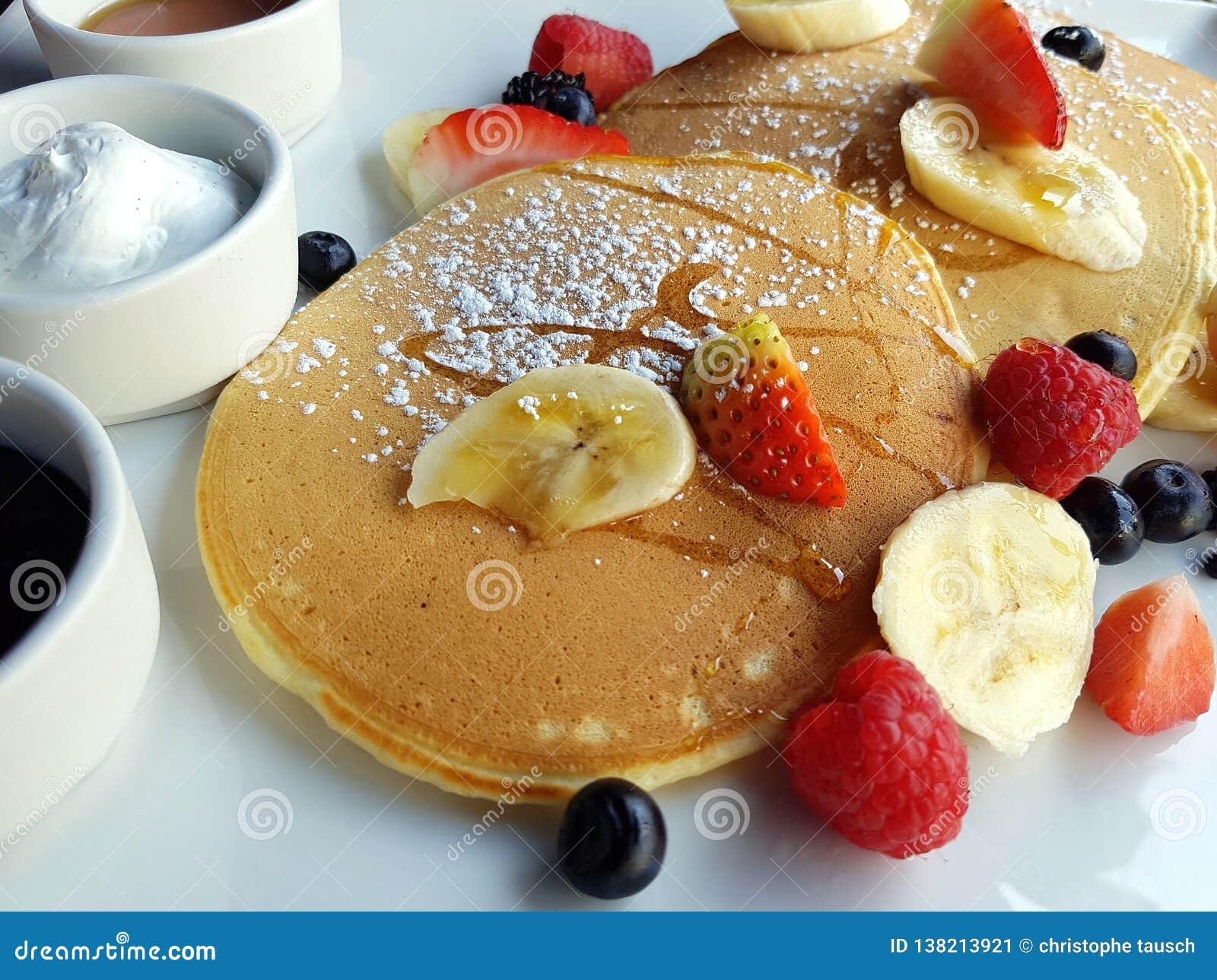 Imagen del primer de un desayuno dulce integrado por crepes, bayas y frutas frescas, queso del ricotta, atasco y miel