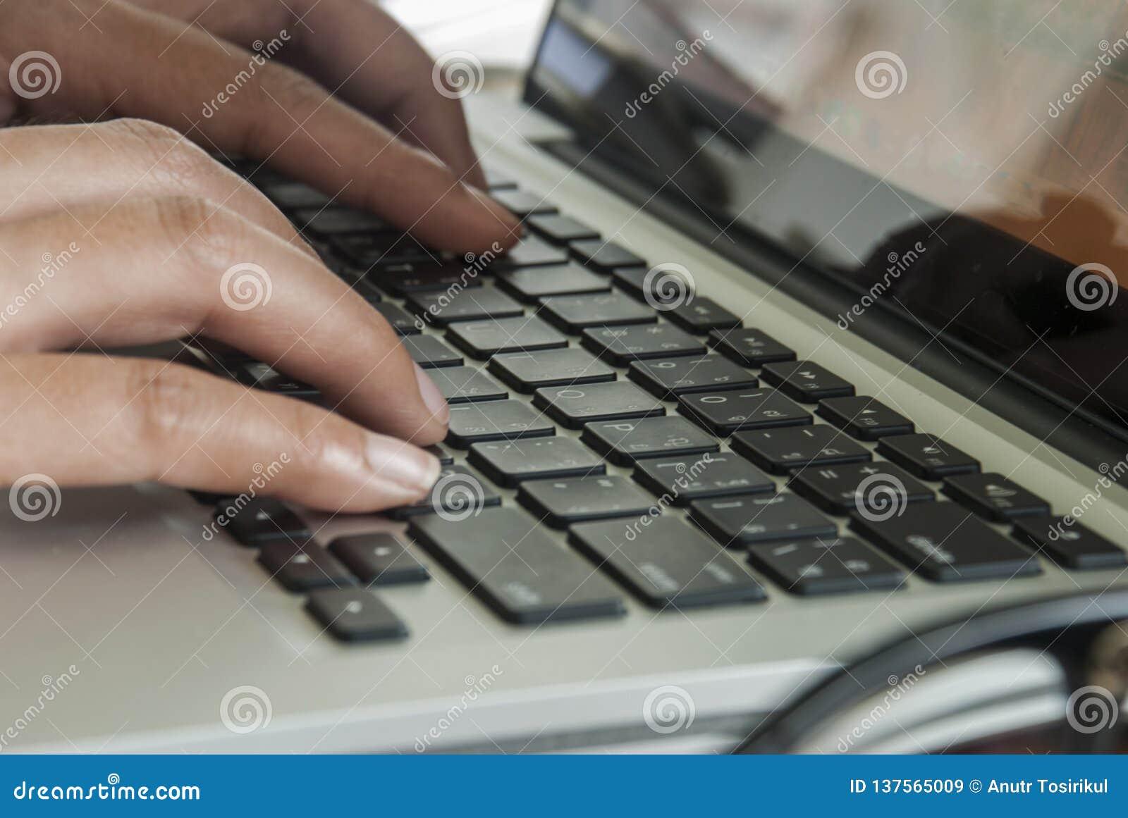 Imagen del primer de una mujer joven que está mecanografiando en un ordenador portátil