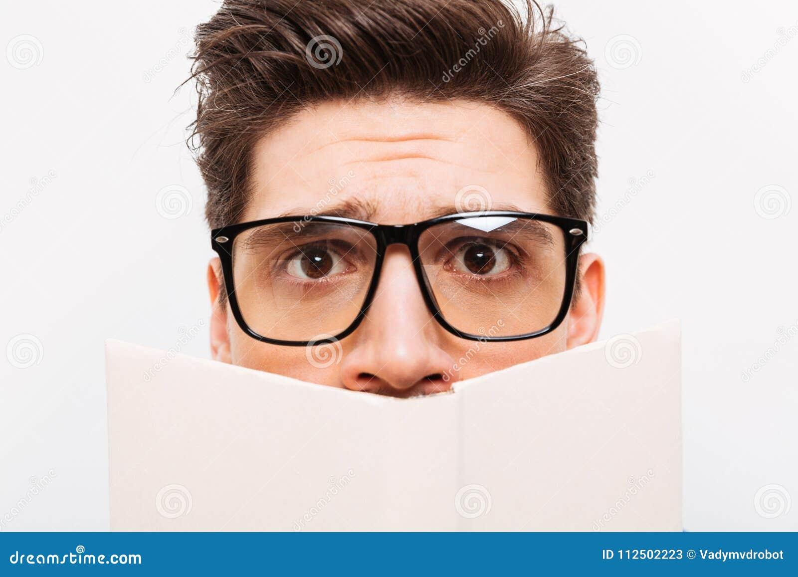Imagen del primer del empollón confuso en las lentes que ocultan detrás del libro