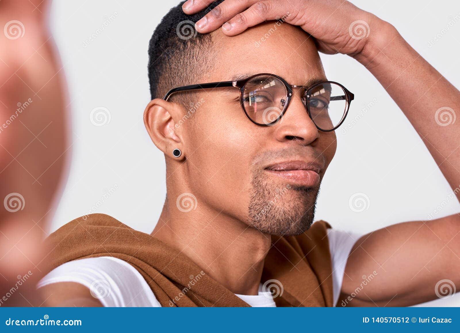 Imagen del primer del hombre joven afroamericano hermoso gafas que sonríe, el llevar, mirando la cámara y tomando el autorretrato