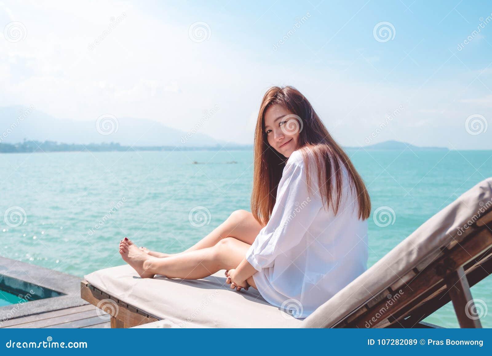 Imagen del retrato de una mujer asiática hermosa feliz en el vestido blanco que se sienta en cama del sol por el mar