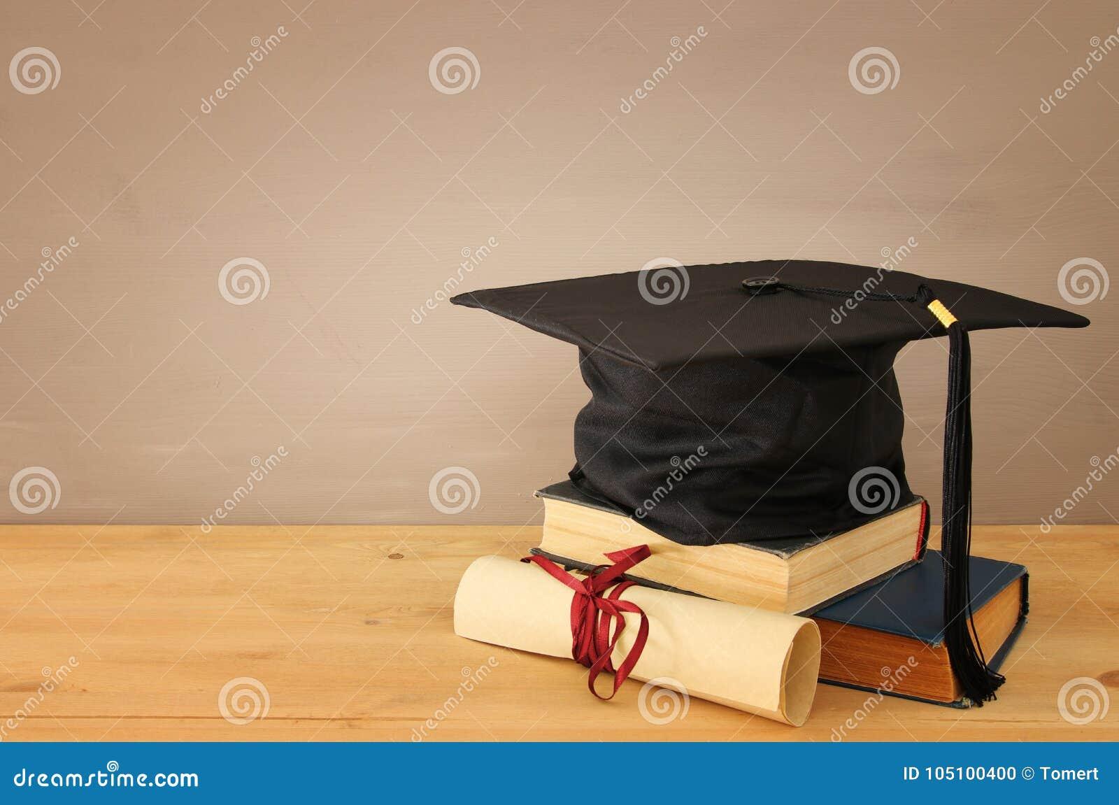 Imagen del sombrero negro de la graduación sobre los libros viejos al lado de la graduación en el escritorio de madera Educación