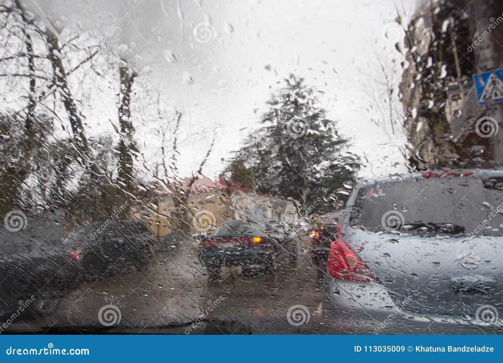 Imagen enfocada del De de la lluvia que baja en el camino, mirando hacia fuera la ventana Silueta borrosa del coche