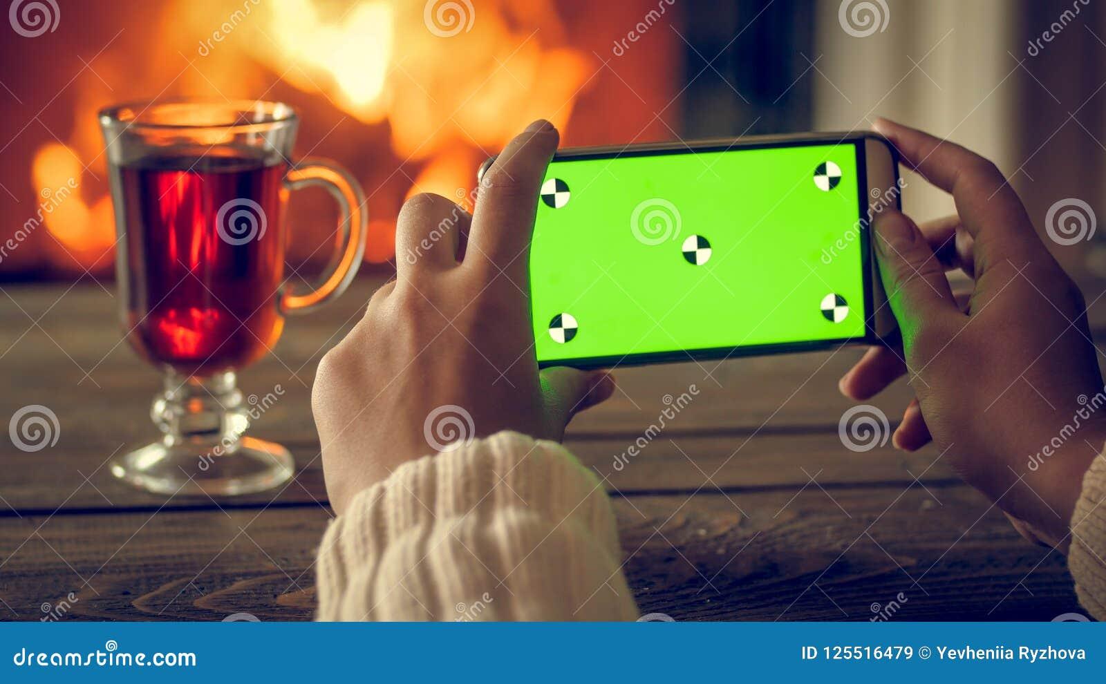Imagen entonada del primer de las manos femeninas que hacen la foto en el smartphone del té y de la chimenea ardiente en la noche