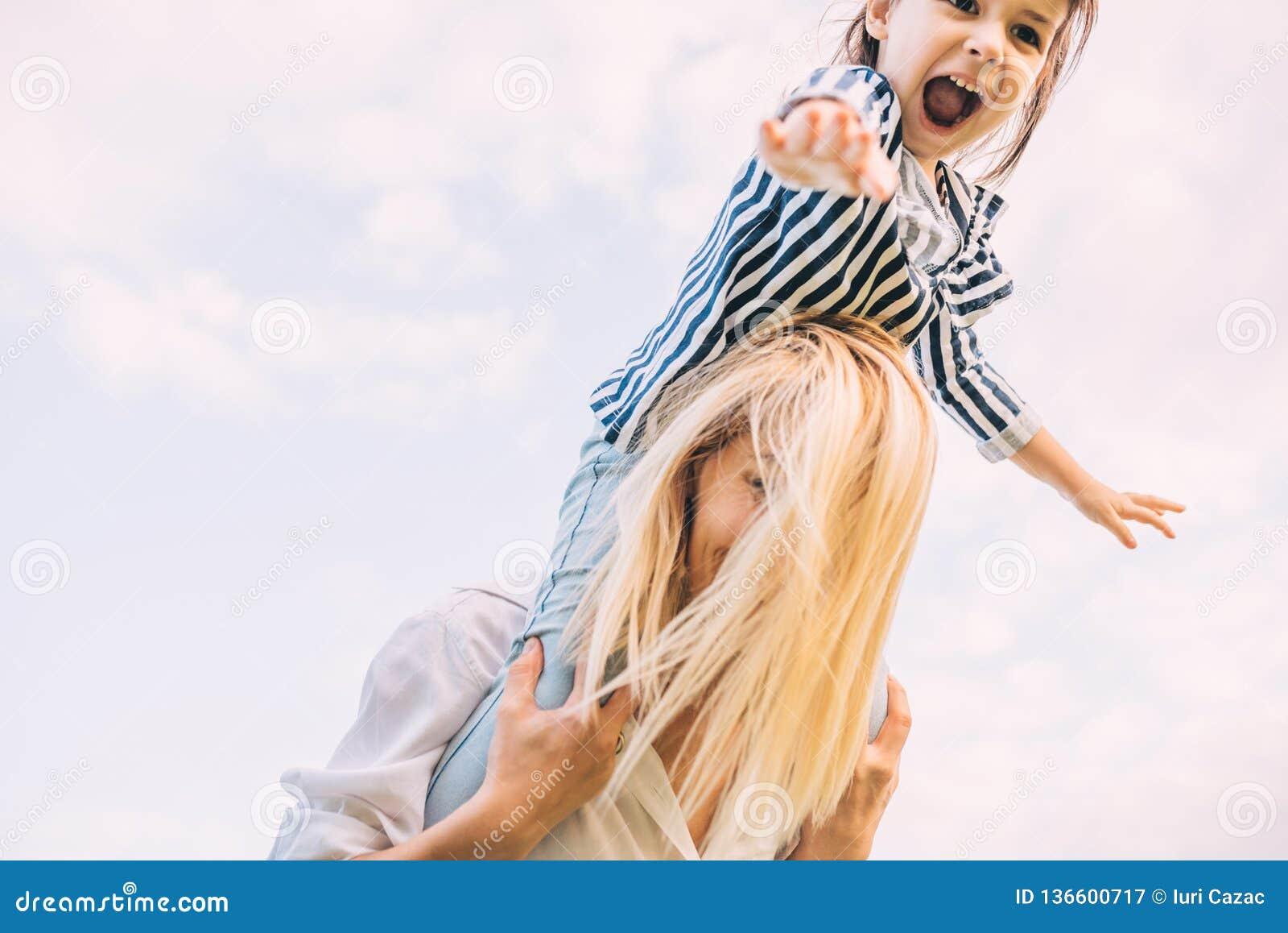 Imagen horizontal de feliz poca hija en un paseo del transporte por ferrocarril con su madre sonriente en fondo del cielo Mujer y