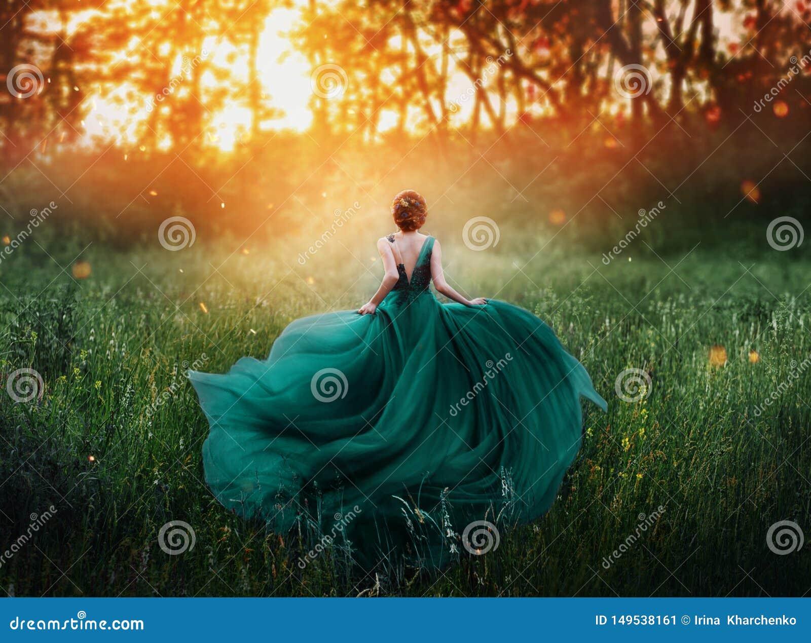 Imagen m?gica, muchacha con funcionamientos rojos del pelo en bosque misterioso oscuro, se?ora en verde esmeralda costoso real el