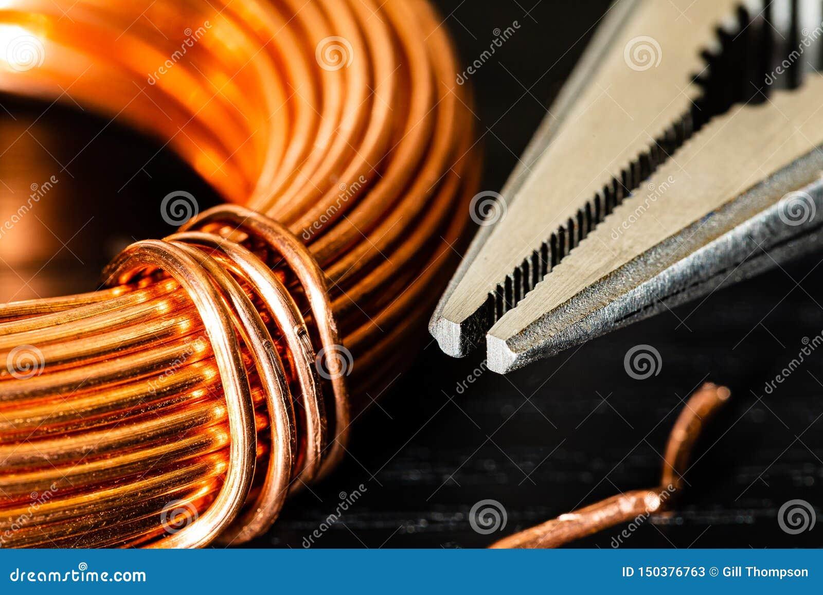 Imagen macra de una bobina del alambre de cobre y de un par de alicates de punta de aguja