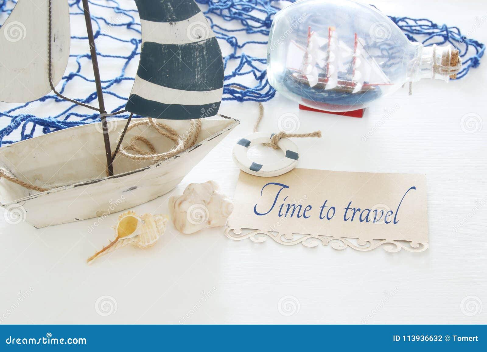 Imagen náutica del concepto con el barco, las conchas marinas y la nota decorativos blancos de vela sobre la tabla de madera blan
