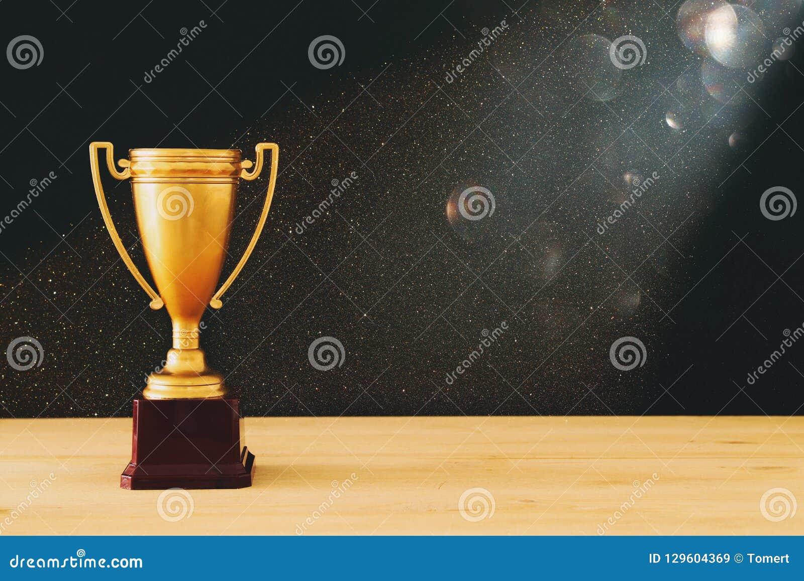 Imagen oscura del trofeo del oro sobre la tabla de madera y el fondo oscuro, con las luces abstractas del brillo