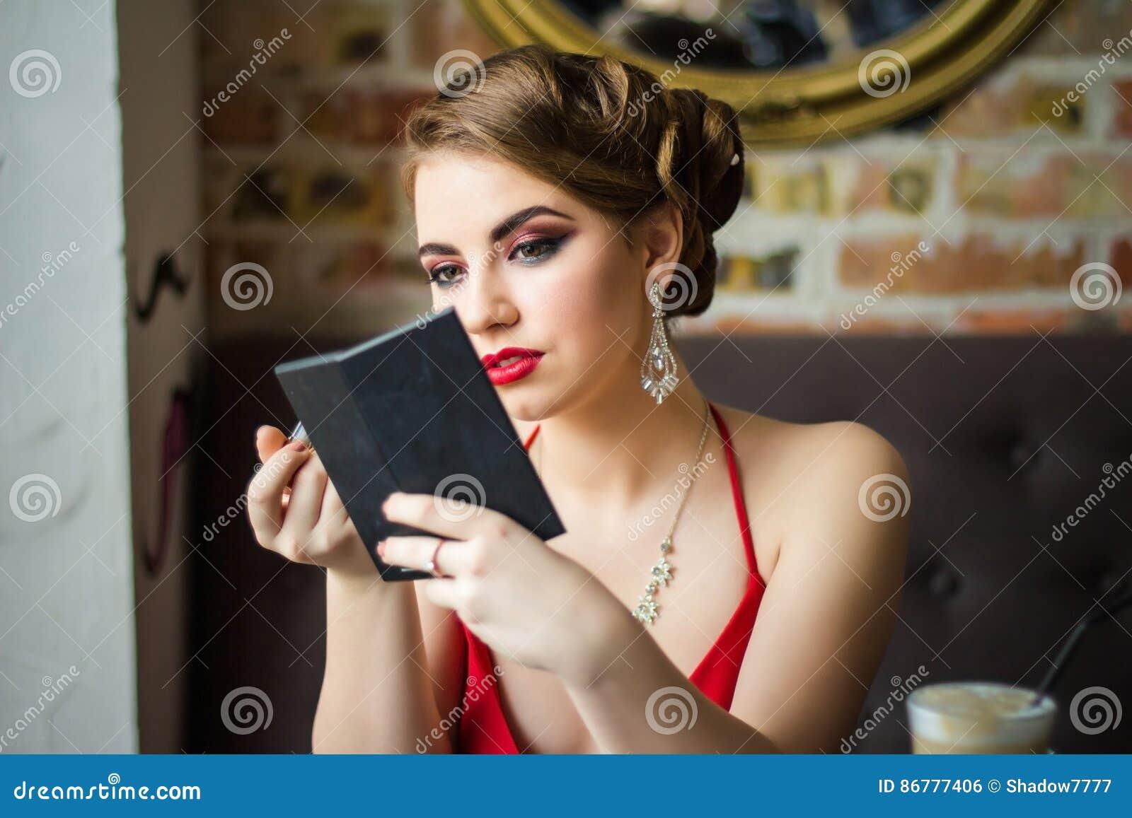 Imagen retra La muchacha pinta su lápiz labial del rojo de los labios