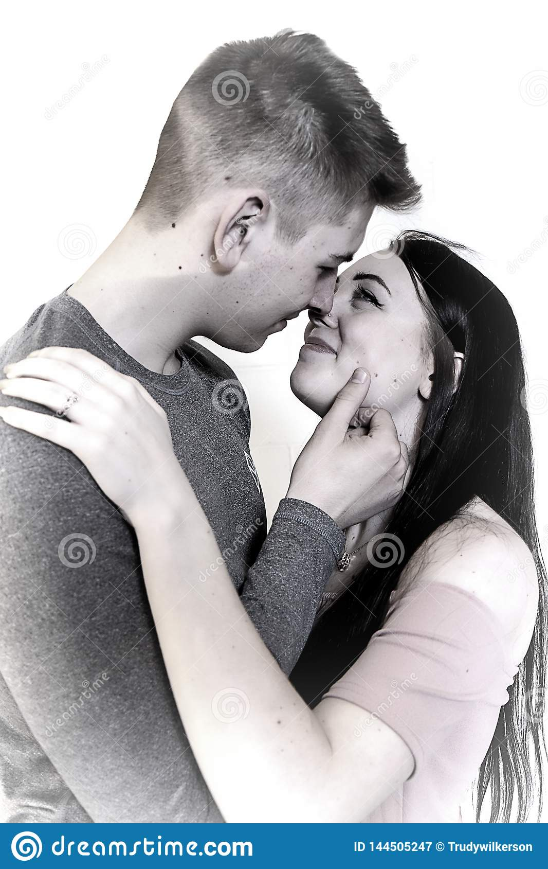Imagen soñadora de los pares que abrazan con el anillo de compromiso en mano izquierda Aislado en blanco