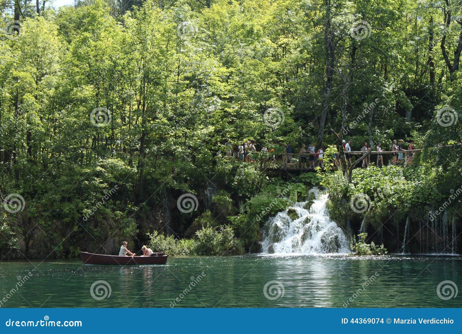Imbarcazione a remi in una dei laghi e della gente Plitvice che camminano su un percorso