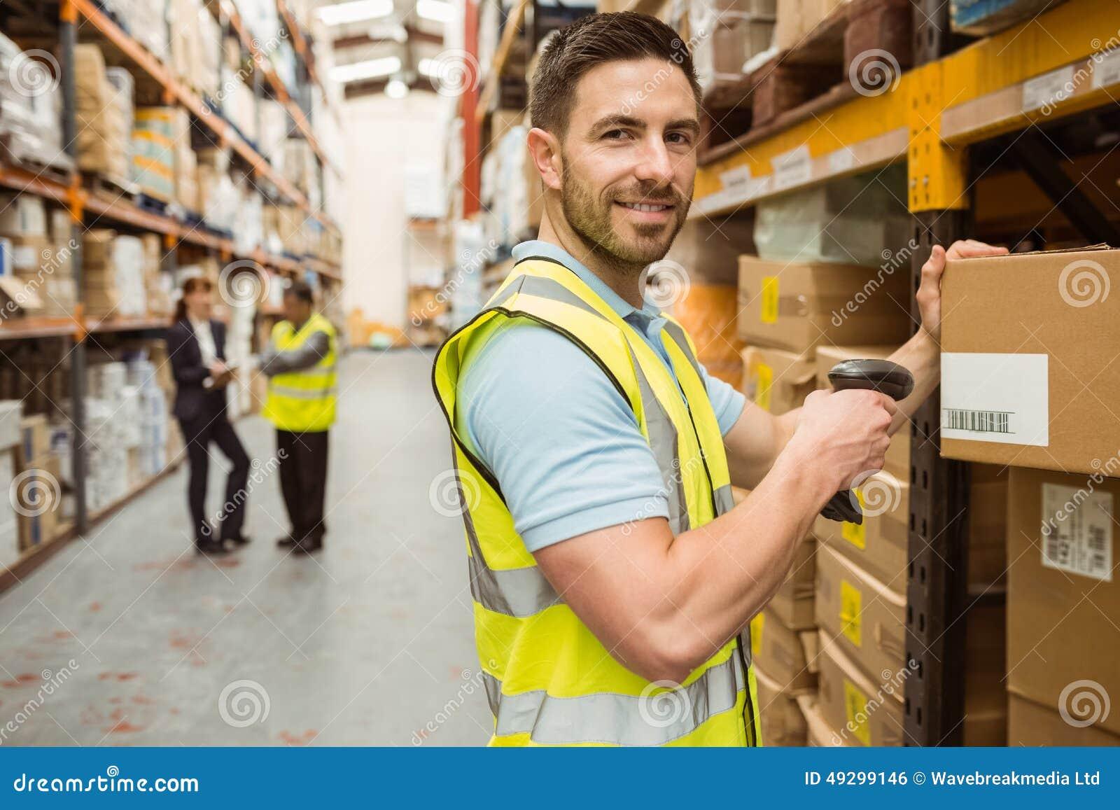 Immagazzini la scatola di esame del lavoratore mentre sorridono alla macchina fotografica