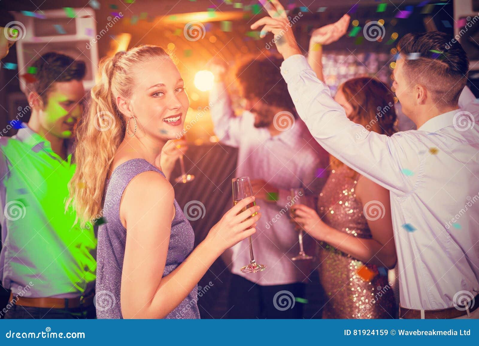 Immagine composita della donna che tiene vetro di champagne mentre ballando con gli amici