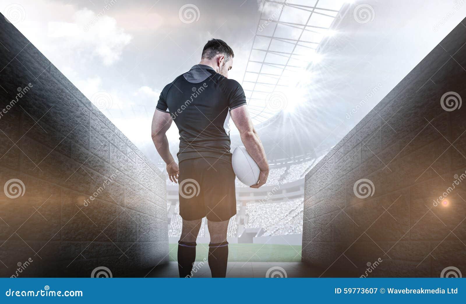 Immagine composita della palla dura della tenuta del giocatore di rugby