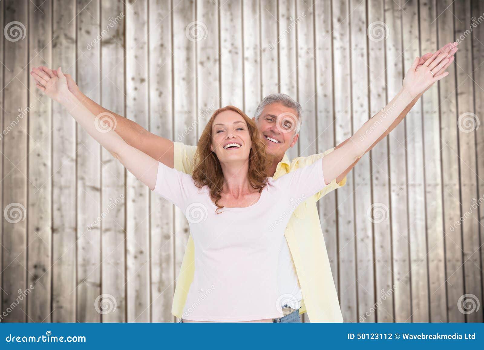 Immagine composita delle coppie casuali che sorridono con le armi alzate