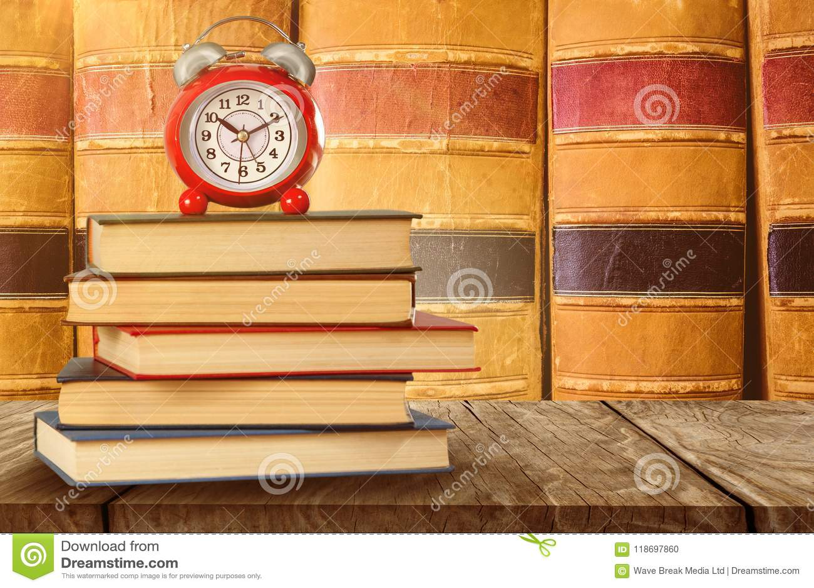 Immagine composita di vecchie sveglia e pila di libri