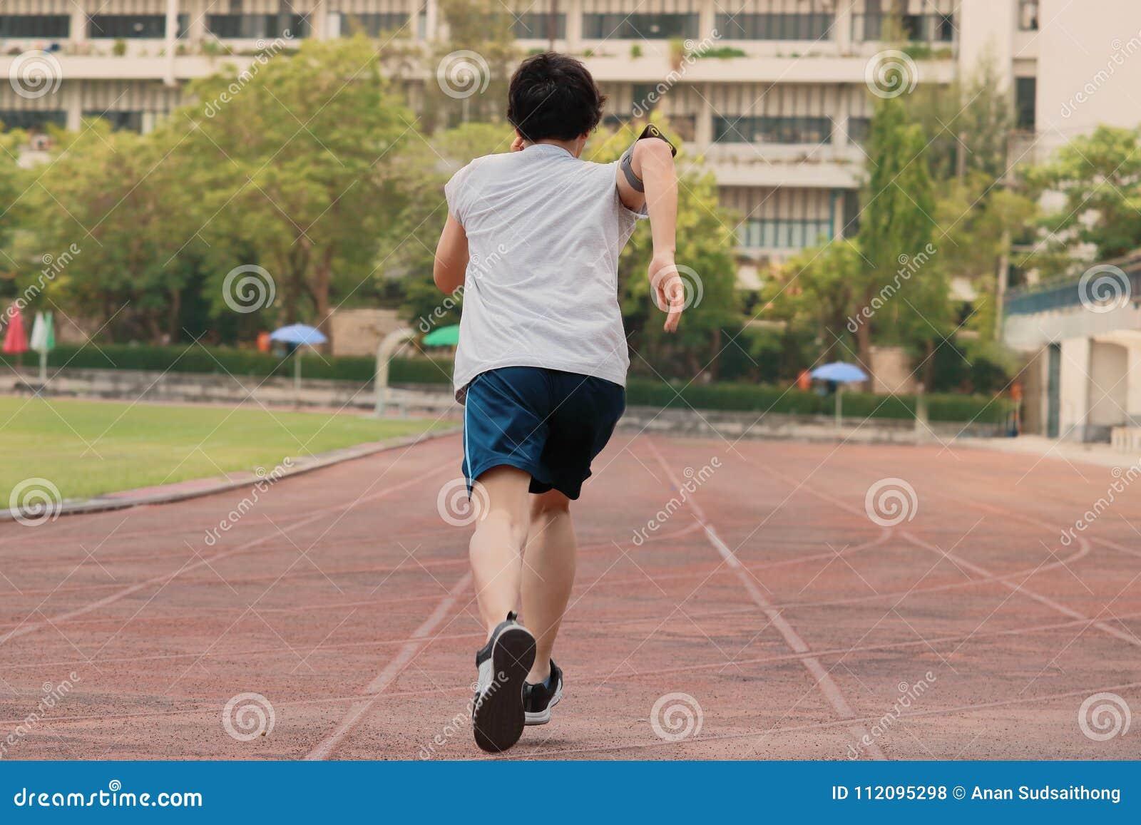 Immagine d annata del filtro del punto di vista posteriore di giovane sprinter asiatico che lascia iniziare sulla pista allo stad