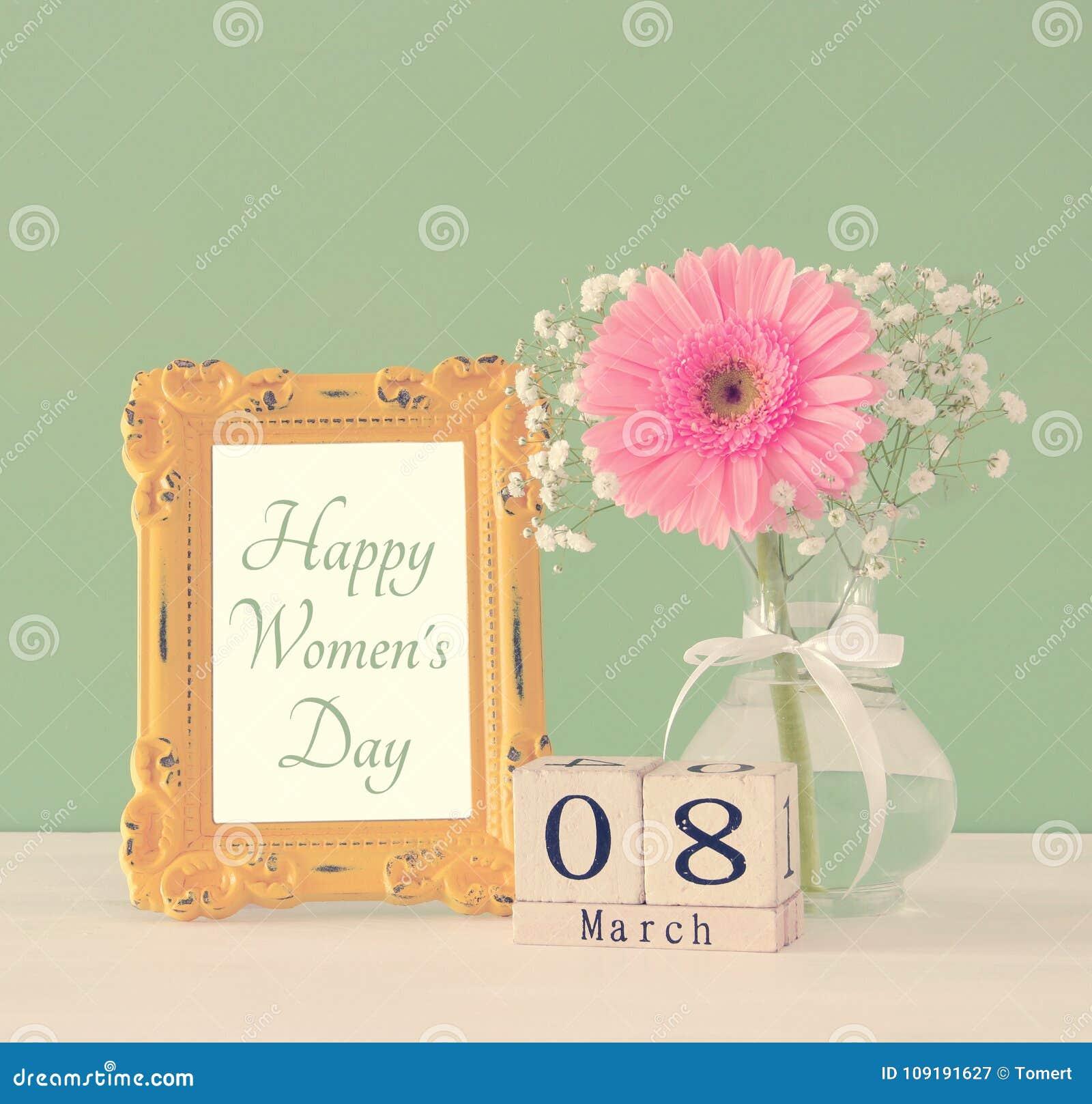 Immagine del concetto internazionale di giorno delle donne con il bello fiore nel vaso sulla tavola di legno