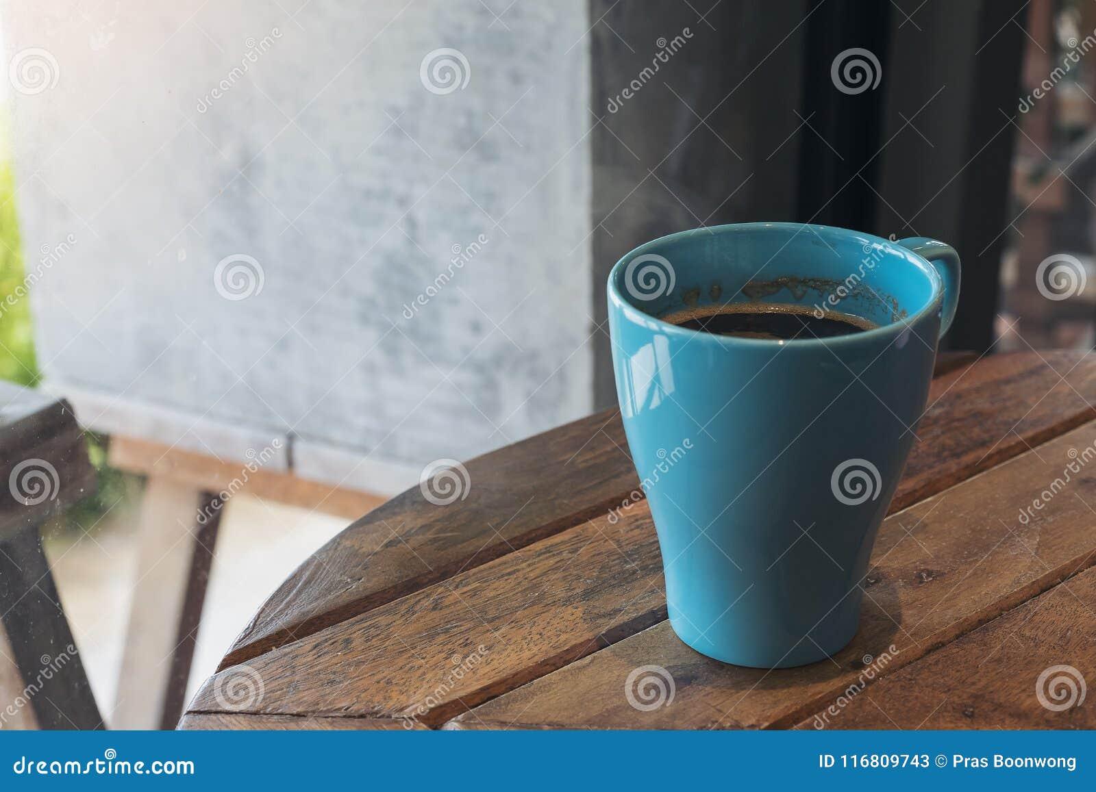 Immagine del primo piano di una tazza blu di caffè caldo sulla tavola di legno d annata