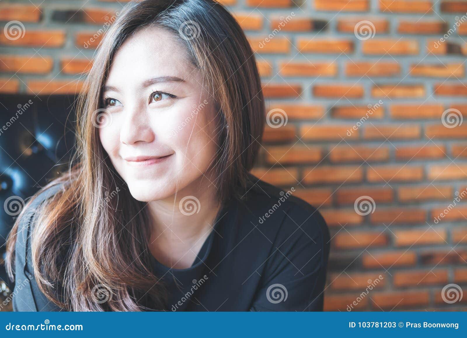 Immagine del ritratto del primo piano di bella donna asiatica con il fronte sorridente e sentiresi bene